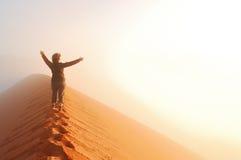 站立在沙丘顶部在沙漠和看在薄雾的人朝阳用手,旅行在非洲 免版税库存图片
