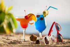 站立在沙子的五颜六色的鸡尾酒 库存图片