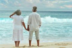 站立在沙滩的年长夫妇背面图在sunse期间 库存图片