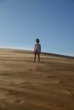 站立在沙漠的女孩 图库摄影