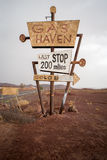 站立在沙漠的高葡萄酒气体标志 免版税图库摄影