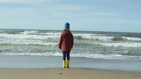 站立在沙滩和休息的明亮的黄色胶靴的孤独的小女孩 逗人喜爱的女性看波浪 影视素材