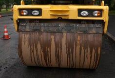 站立在沥青的黄色沥青路辗 免版税库存照片