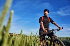 站立在河上的小山的年轻骑自行车者的画象反对与云彩的蓝天 免版税图库摄影