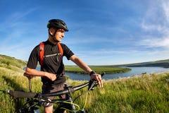 站立在河上的小山的年轻骑自行车者的画象反对与云彩的蓝天 免版税库存图片