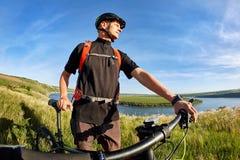 站立在河上的小山的年轻骑自行车者的画象反对与云彩的蓝天 免版税库存照片