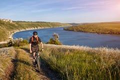 站立在河上的小山的年轻骑自行车者的画象反对与云彩的蓝天 库存照片