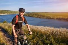 站立在河上的小山的年轻骑自行车者的画象反对与云彩的蓝天 库存图片