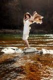 站立在河和使用的岩石的美丽的妇女旅客 免版税库存图片