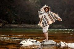 站立在河和使用的岩石的美丽的妇女旅客 免版税图库摄影