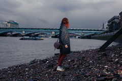 站立在河岸的少妇在城市 免版税库存照片