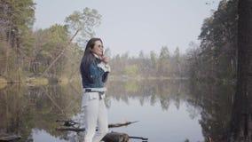 站立在河岸的白色裤子、牛仔裤夹克和太阳镜的俏丽的年轻女人 女孩是冷的,她摩擦 影视素材