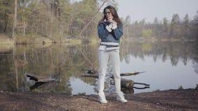 站立在河岸的白色裤子、牛仔裤夹克和太阳镜的逗人喜爱的年轻女人 女孩是冷的,她摩擦 股票视频