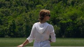 站立在河桥梁和山的少妇盖了背景的绿色森林 享受湖和绿色的女孩 股票视频