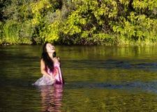 站立在河的微笑的日裔美国人妇女 免版税库存照片