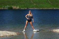 站立在河的白肤金发的健身女孩 免版税库存图片