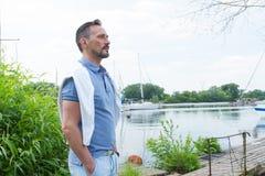 站立在河码头的英俊的年轻yachtman 供以人员调查他的游艇 与他的游艇的年轻商人在小游艇船坞 库存照片