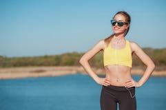 站立在河背景的适合少妇体育胸罩的和耳机室外射击用她的在臀部的手和sungla的 库存照片