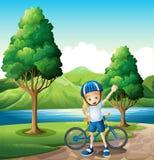 站立在河附近的一个年轻女性骑自行车的人 免版税库存图片