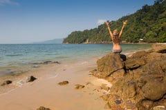站立在沿海海岩石的女孩 福利健康生活方式 免版税库存图片