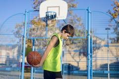 站立在法院的年轻蓝球运动员佩带黄色s 免版税图库摄影