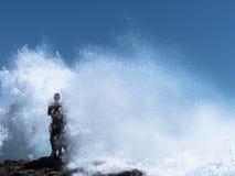 站立在波浪的一个岩石的两个人 图库摄影