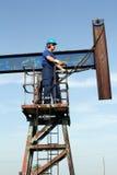站立在泵浦起重器的蓝色制服的工作者 免版税图库摄影