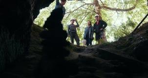 站立在洞的入口的小组愉快的朋友探险家在森林里 股票录像