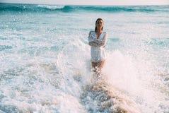 站立在浪花和泡沫的一个女孩的特写镜头对腰部在水中,穿戴在时兴的白色 库存照片