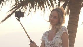 站立在海和做selfie照片的滑稽的女孩在电话使用monopod 影视素材