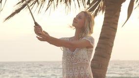 站立在海和做selfie照片的滑稽的女孩在电话使用monopod 股票录像