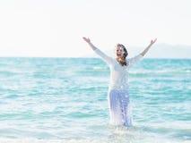 站立在海和洒的微笑的少妇水 库存图片