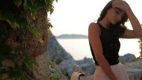 站立在海岸和调直头发的可爱的妇女在夏天晚上 影视素材