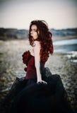站立在海岸的美丽的哀伤的goth女孩 查出的背面图白色 库存照片