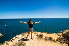 站立在海洋和欢迎上的一个岩石的美丽的拉丁妇女夏天 免版税库存照片