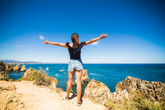 站立在海洋和欢迎上的一个岩石的美丽的拉丁妇女夏天 库存照片