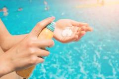站立在海滩和使用suncream的妇女 关闭接受sunblock奶油色lotio的妇女手 库存图片