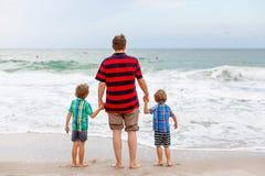 站立在海滩海洋和看在天际的两个愉快的小孩男孩和父亲在风暴日 家庭,爸爸 免版税图库摄影