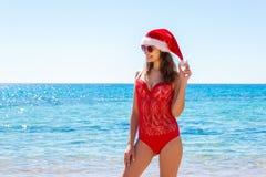 站立在海滩的圣诞老人帽子的少妇 圣诞节连接了特别是空的行业互联网膝上型计算机办公室照片与结构树usb假期有关 复制空间 免版税库存照片
