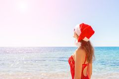 站立在海滩的圣诞老人帽子的少妇 圣诞节连接了特别是空的行业互联网膝上型计算机办公室照片与结构树usb假期有关 复制空间 图库摄影