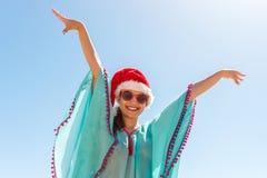 站立在海滩的妇女用她的手由天空决定,戴圣诞老人帽子 免版税库存图片