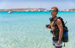 站立在海滩的男性轻潜水员 免版税库存照片