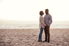站立在海滩的美满的年轻非洲夫妇在黄昏 免版税库存图片