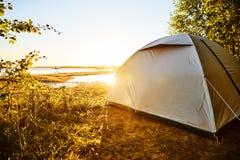 站立在海滩野营的斑点的白色帐篷在湖Vänern在瑞典 太阳是光亮的和很快是日落 帐篷是替换者 免版税图库摄影