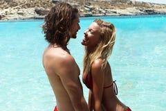 站立在海的年轻性感的被晒黑的夫妇在蓝色热带盐水湖,看彼此与柔软,爱概念,移动 免版税库存照片