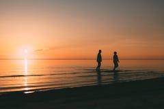 站立在海的成人夫妇剪影反对日落 库存照片