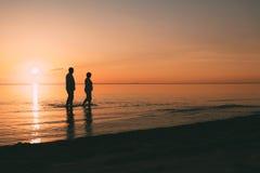 站立在海的成人夫妇剪影反对日落 免版税库存图片