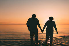 站立在海的成人夫妇剪影反对日落 库存图片