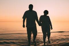 站立在海的成人夫妇剪影反对日落 图库摄影