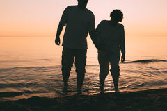 站立在海的成人夫妇剪影反对日落 免版税库存照片